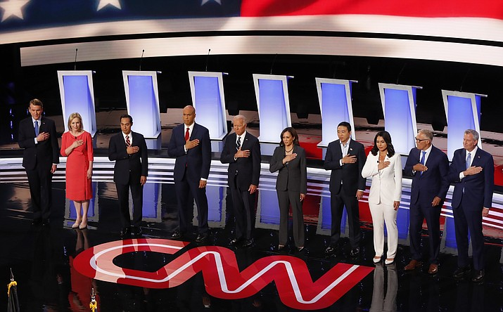 From left, Sen. Michael Bennet, D-Colo., Sen. Kirsten Gillibrand, D-N.Y., former Housing and Urban Development Secretary Julian Castro, Sen. Cory Booker, D-N.J., former Vice President Joe Biden, Sen. Kamala Harris, D-Calif., Andrew Yang, Rep. Tulsi Gabbard, D-Hawaii, Washington Gov. Jay Inslee and New York City Mayor Bill de Blasio stand for the National Anthem as they are introduced before the second of two Democratic presidential primary debates hosted by CNN Wednesday, July 31, 2019, in the Fox Theatre in Detroit. (Paul Sancya/AP)
