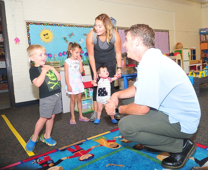 Russell Shepherd, with his family, Charlotte, Julie and Freddie, greets his new teacher, Ryan Keim, at Discovery Gardens preschool at Washington School in Prescott on Tuesday. (Les Stukenberg/Courier)