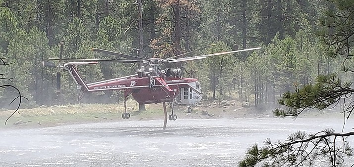 A helicopter tanker pulls in water during a recent wildland firefighting operation at the Museum Fire recently north of Flagstaff. Tuesday, the fire received rain into the afternoon, bringing much-needed moisture, but also pausing suppression repair efforts. Crews were to continue that work Wednesday. Courtesy of U.S. Forest Service