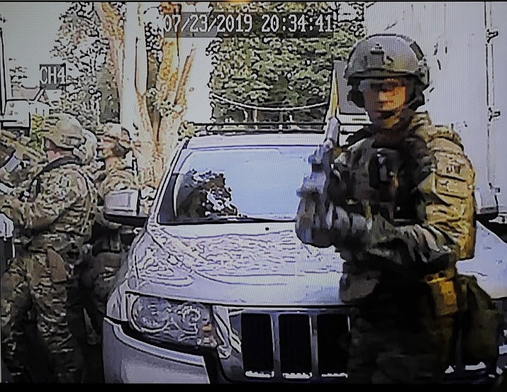 In this image made from a Monday, July 29, 2019, security camera video provided by a neighbor who has requested not to be identified, federal agents conduct a raid on the home of Paige A. Thompson in Seattle. Thompson is accused of accessing the personal information of millions of Capital One credit card holders or credit card applicants in the U.S. and Canada. The time and date stamp on the image is inaccurate, as the raid took place on Monday, July 29, 2019. (Courtesy Photo)
