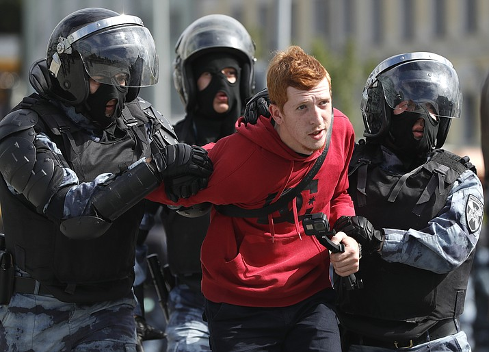 Police officers detain a protestor during an unsanctioned rally in the center of Moscow, Russia, Saturday, Aug. 3, 2019. Police in Moscow have detained a leading opposition figure as she was heading to an unauthorized rally and march protesting the exclusion of independent and opposition candidates from the Moscow city council election. Lyubov Sobol, who is one of the aspirants rejected from the ballot, has been detained in central Moscow and taken away in a police van. Police have detained dozens of other demonstrators. (AP Photo/ Pavel Golovkin)