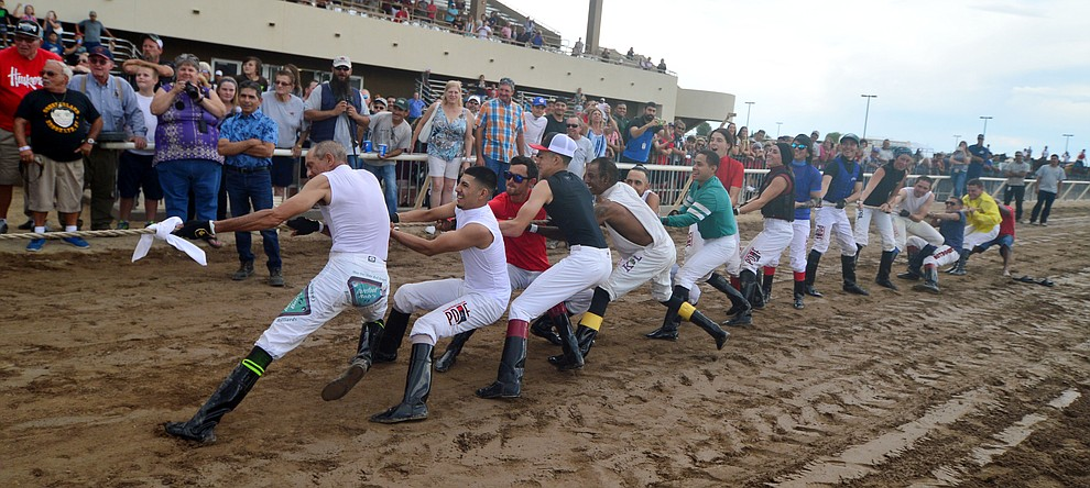 Jockeys from Arizona Downs dig deep as they take on Bradshaw Mountain High School football players in a tug-a-war Saturday, August 3, 2019, in on the racetrack in Prescott Valley.  (Les Stukenberg/Courier)