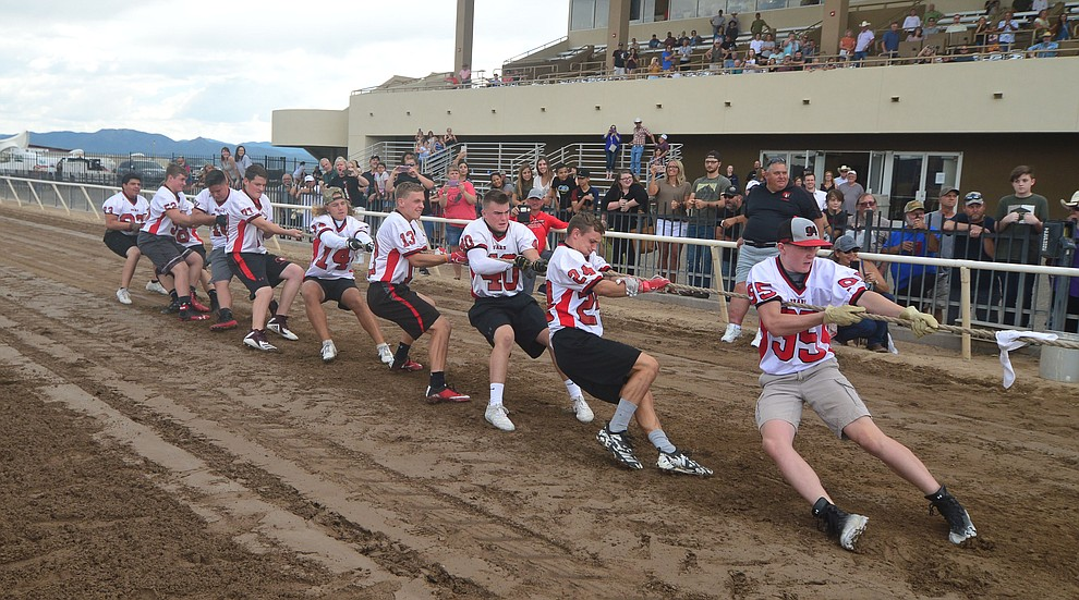 Bradshaw Mountain High School football players pull hard as they take on the jockeys from Arizona Downs in a tug-a-war Saturday, August 3, 2019, in on the racetrack in Prescott Valley.  (Les Stukenberg/Courier)