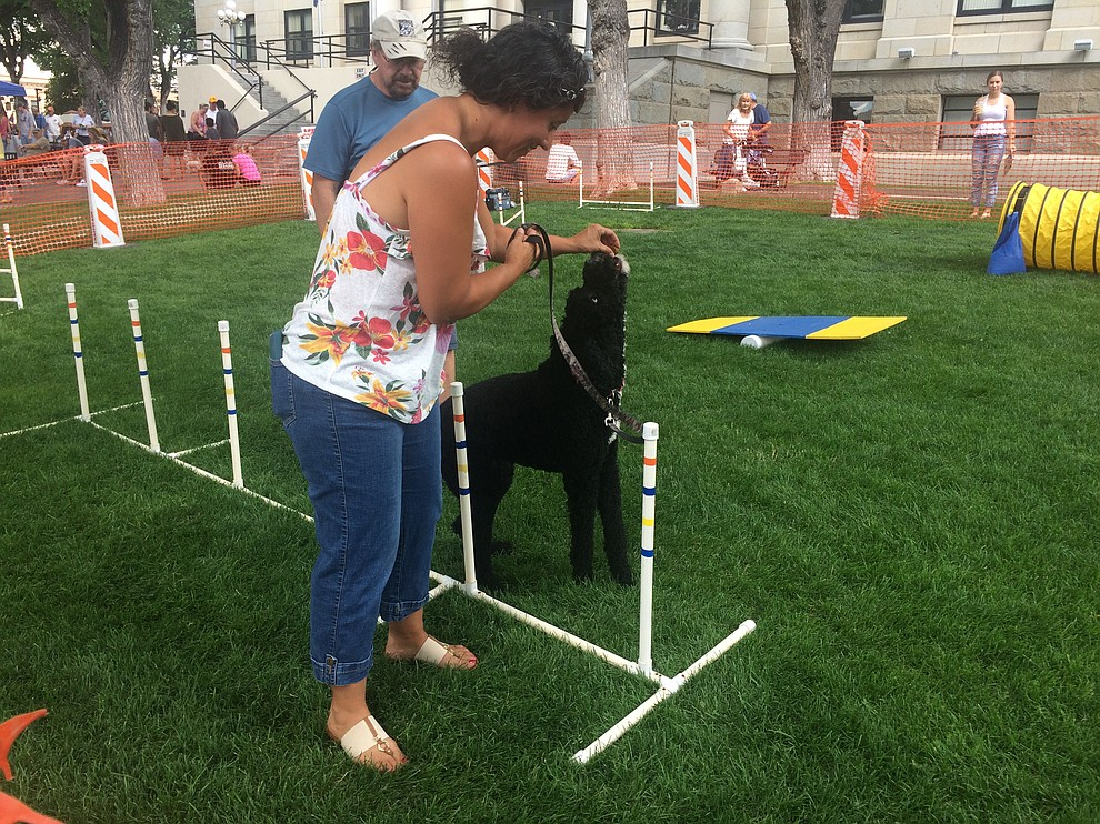 Michele Keck gives her dog, Luna, a treat while taking her through the agility course at the Woof Down Lunch event at courthouse plaza Saturday, Aug. 3. (Jason Wheeler/Courier)
