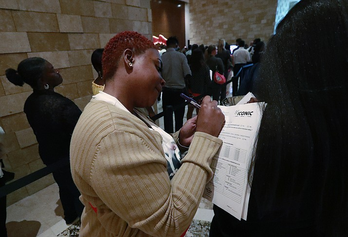 Job applicant Esta Williams, center, uses Tracy Simeton's back to fill out a questionnaire as they wait in line at the Seminole Hard Rock Hotel & Casino Hollywood during a job fair June 4, 2019, in Hollywood, Fla. (Wilfredo Lee/AP, File)