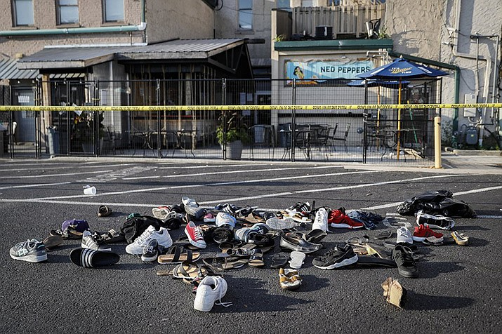 Shoes are piled outside the scene of a mass shooting including Ned Peppers bar, Sunday, Aug. 4, 2019, in Dayton, Ohio. (AP Photo/John Minchillo)