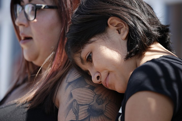 Eleven-year-old Leilani Hebben puts her head on her mother Anabel Hebben's shoulder as they visit the scene of a mass shooting at a shopping complex Sunday, Aug. 4, 2019, in El Paso, Texas. (AP Photo/John Locher)