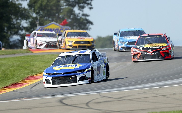 """Chase Elliott leads the field thought the area known as """"The Bus Stop"""" during a NASCAR Cup Series auto race at Watkins Glen International, Sunday, Aug. 4, 2019, in Watkins Glen, N.Y. (John Munson/AP)"""