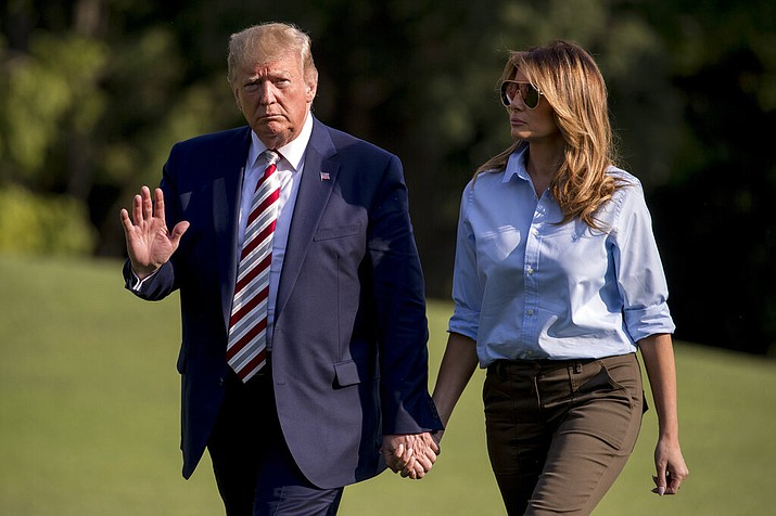President Donald Trump waves to members of the media as he and first lady Melania Trump walk across the South Lawn of the White House in Washington, Sunday, Aug. 4, 2019, as they return from Bedminster, N.J. (AP Photo/Andrew Harnik)