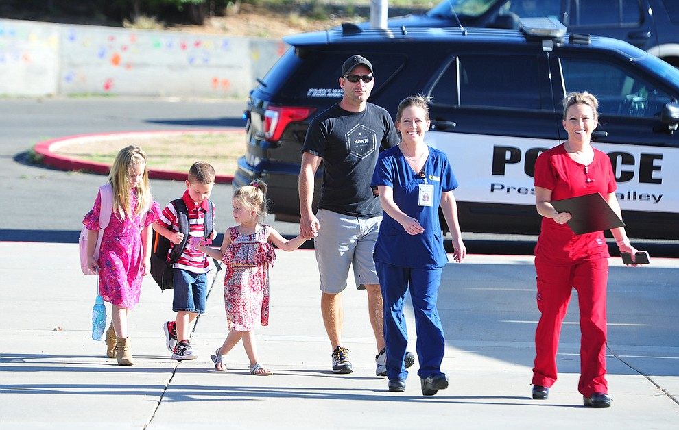 Lilly Zeller, Parker Woods, Payton Woods, Brett Woods, Lauren Zeller and Jackie Woods walk up the entranceway as students in the Humboldt Unified School District returned to school at Coyote Springs Elementary School Monday, August 5, 2019, in Prescott Valley.  (Les Stukenberg/Courier)