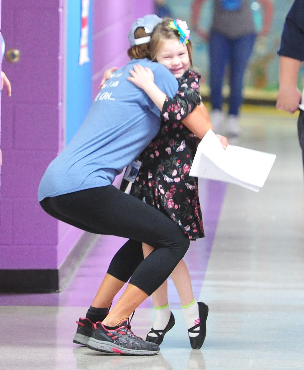 First grader Olivia Langston greets kindergarten teacher Rachel Leuschner as students in the Humboldt Unified School District returned to school at Coyote Springs Elementary School Monday, August 5, 2019, in Prescott Valley.  (Les Stukenberg/Courier)