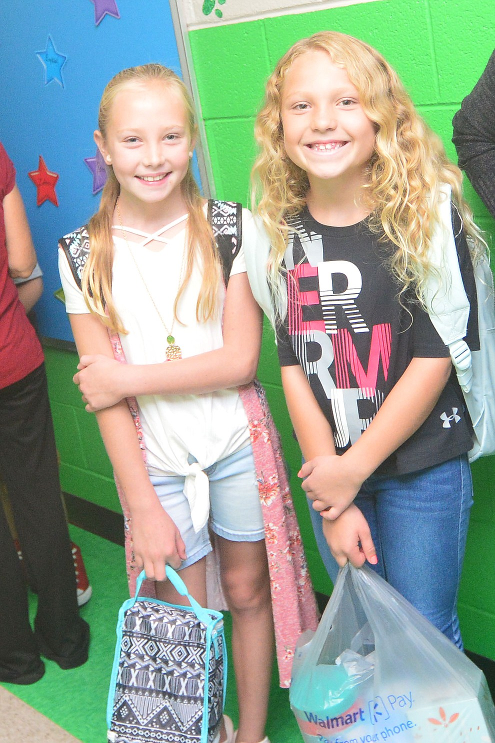 Fourth graders Ava Dittert and Raquel Jimenz wait for teachers to return from their morning duties as students in the Humboldt Unified School District returned to school at Coyote Springs Elementary School Monday, August 5, 2019, in Prescott Valley.  (Les Stukenberg/Courier)