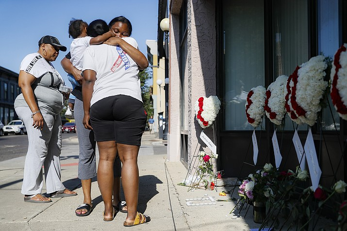 "Family members of slain mass shooting victim Thomas ""TJ"" McNichols, from left, Donna Johnson, aunt, and sisters Jamila and Finesse McNichols, mourn beside a memorial near the scene of the shooting Monday, Aug. 5, 2019, in Dayton, Ohio. (AP Photo/John Minchillo)"