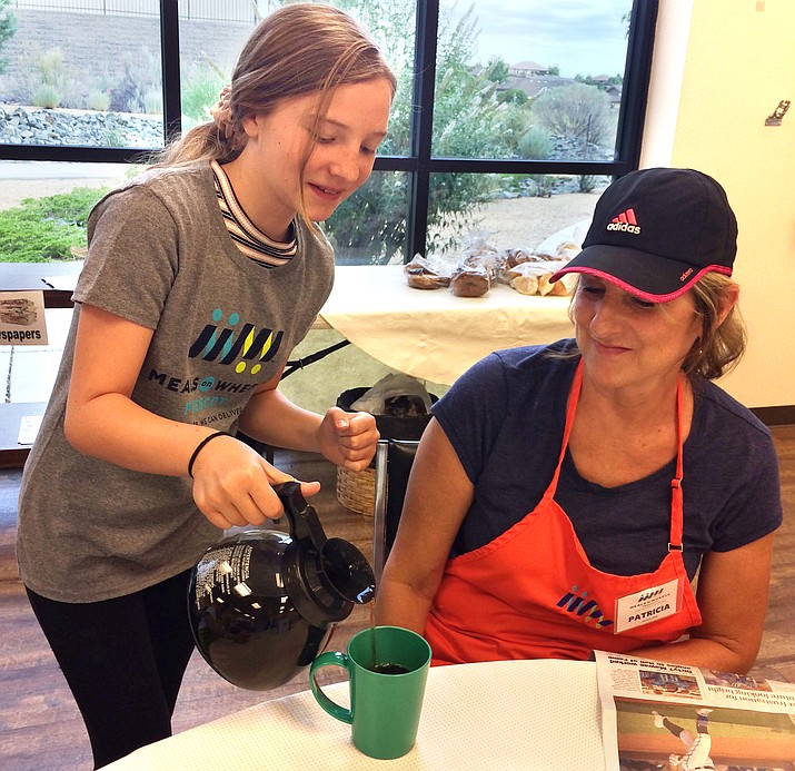 Teen Charm Ranzi pours a second cup of coffee for Meals on Wheels adult volunteer Patricia Kerfoot. (Nancy Hutson/Courier)