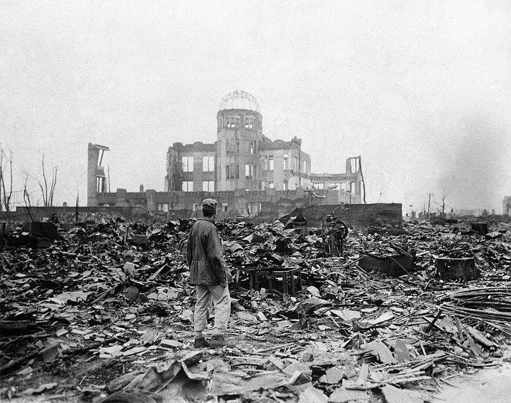 In this Sept. 8, 1945 file photo, an journalist stands on rubble near the shell of a building that once was a movie theater in Hiroshima, Japan, a month after the first atomic bomb ever used in warfare was dropped by the U.S. in World War II. (Stanley Troutman/Associated Press)