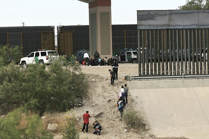 In this June 15, 2019, file photo, migrants cross the Rio Bravo illegally to surrender to the American authorities on the US - Mexico border between Ciudad Juarez and El Paso. El Paso has swiftly become one of the busiest corridors for illegal border crossings in the U.S. after years as one of the sleepiest. (Christian Torres/AP, file)