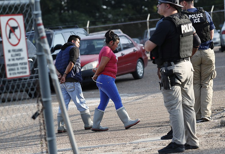 Two people are taken into custody at a Koch Foods Inc. plant in Morton, Miss., on Wednesday, Aug. 7, 2019. U.S. immigration officials raided several Mississippi food processing plants on Wednesday and signaled that the early-morning strikes were part of a large-scale operation targeting owners as well as employees. (AP Photo/Rogelio V. Solis)