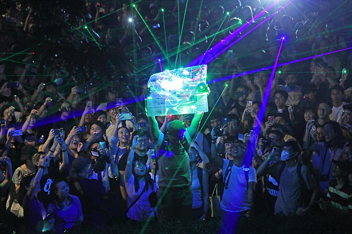 Protesters focus the laser pointers to a newspaper as they try to burn it, during a rally to demonstrate against the arrests of people caught in possession of laser pointers that police classified as offensive weapons because of their ability to harm the eyes in Hong Kong, Wednesday, Aug. 7, 2019.  (AP Photo/Kin Cheung)
