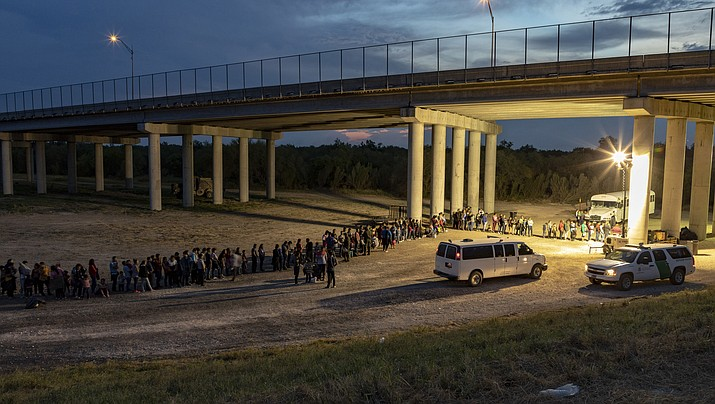 As the sun sets near McAllen, Texas, migrants that have crossed the Rio Grande surrender to U.S. Border Patrol near an area known as Rincon. From here they will be transported to a processing center.(Photo by Mani Albrecht/U.S. Customs and Border Protection)