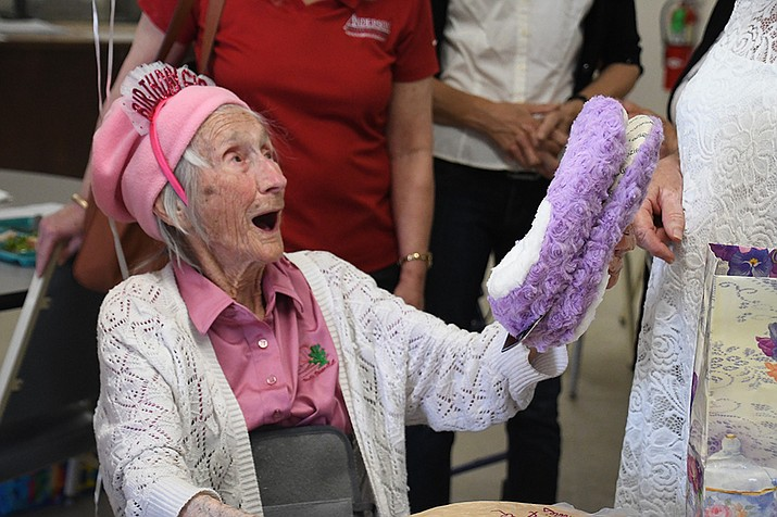 Alphia Dunlop reacts with joy when she received a pair of purple slippers for her 100th birthday Friday. (Photo by Vanessa Espinoza/Daily Miner)
