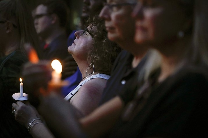 Mourners pause for a prayer as they gather for a vigil at the scene of a mass shooting, Sunday, Aug. 4, 2019, in Dayton, Ohio. In Prescott, the non-partisan community group Prescott Indivisible and Prescott Peacebuilders will host a Candlelight Vigil for the Dayton and El Paso massacre victims from 7 to 8 p.m. Monday, Aug. 12, at the courthouse plaza in downtown Prescott. (AP Photo/John Minchillo)