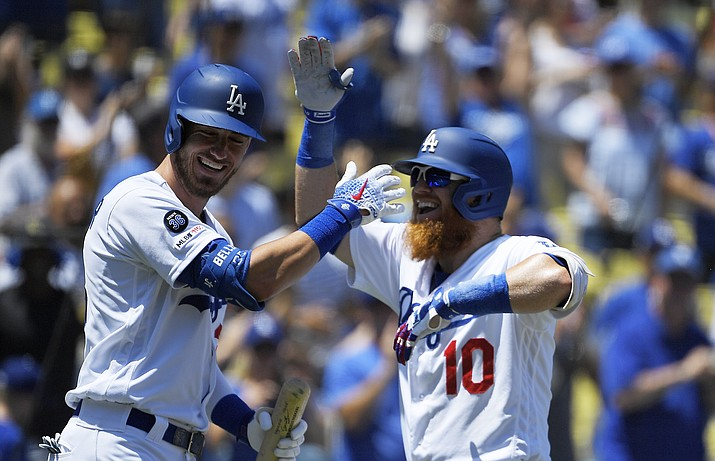 Los Angeles Dodgers' Justin Turner, right, is congratulated by Cody Bellinger after hitting a two-run home run during the first inning of a baseball game against the Arizona Diamondbacks Sunday, Aug. 11, 2019, in Los Angeles. (Mark J. Terrill/AP)