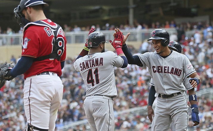 Cleveland Indians' Carlos Santana, center, is welcomed by pinch runner Oscar Mercado, right's Santana scores on his grand slam off Minnesota Twins pitcher Taylor Rogers in the 10th inning of a baseball game Sunday, Aug. 11, 2019, in Minneapolis. The Indians won 7-3. At left is Twins catcher Mitch Garver. (Jim Mone/AP)
