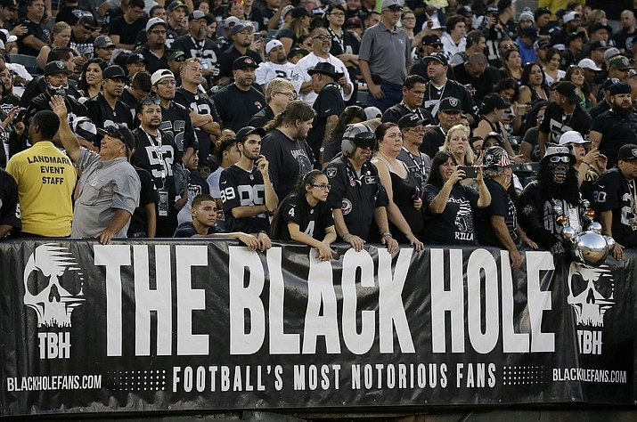 "In this Aug. 31, 2017, file photo, Oakland Raiders fans watch from the Black Hole section of Oakland Alameda County Coliseum during the first half of an NFL preseason football game between the Raiders and the Seattle Seahawks in Oakland, Calif. The slow, agonizing demise of the Oakland Raiders will continue for at least one more season. There will be one more ""final"" home game at the Oakland Coliseum, Dec. 15 against the Jacksonville Jaguars. There have been possible ""final"" home games for a few years now because the Raiders have essentially had one foot out the door since 2015, when they joined with the AFC West rival Chargers in a failed attempt to build a stadium in the Los Angeles suburb of Carson. (Eric Risberg/AP, file)"