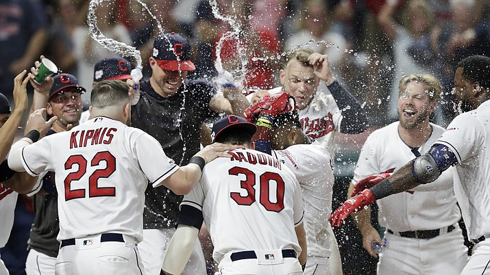 The Cleveland Indians mob Carlos Santana after Santana hit a game-winning solo home run in the ninth inning of a baseball game against the Boston Red Sox, Monday, Aug. 12, 2019, in Cleveland. The Indians won 6-5. (Tony Dejak/AP)