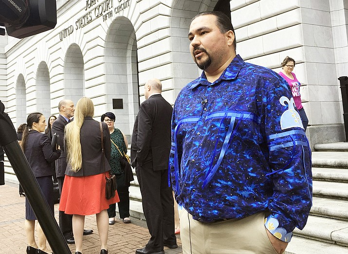 Tehassi Hill, tribal chairman of the Oneida Nation, stands outside a federal appeals court in New Orleans in March, following arguments on the constitutionality of a 1978 law giving Native American families preference in adoption of Native American children. On Aug. 9, the 5th U.S. Circuit Court of Appeals in New Orleans upheld the constitutionality of the law. (AP Photo/Kevin McGill, File)
