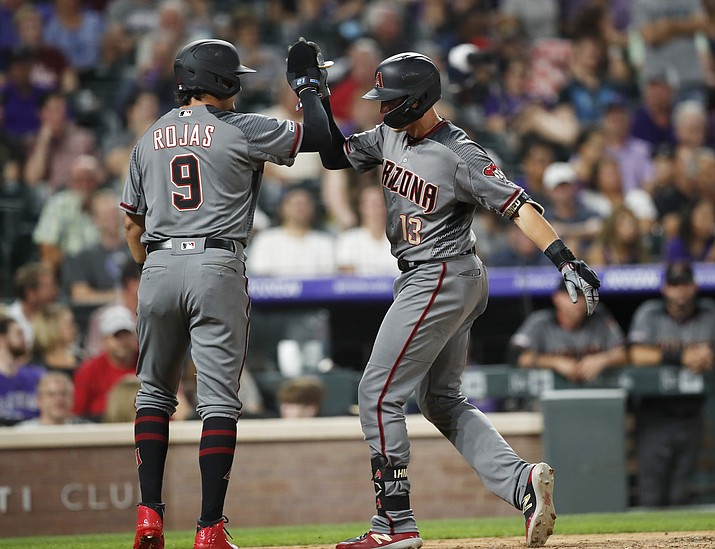 Arizona Diamondbacks' Josh Rojas, left, celebrates with Nick Ahmed as he crosses home plate after hitting a two-run home run off Colorado Rockies relief pitcher Jake McGee in the sixth inning of a baseball game, Monday, Aug. 12, 2019, in Denver. (AP Photo/David Zalubowski)
