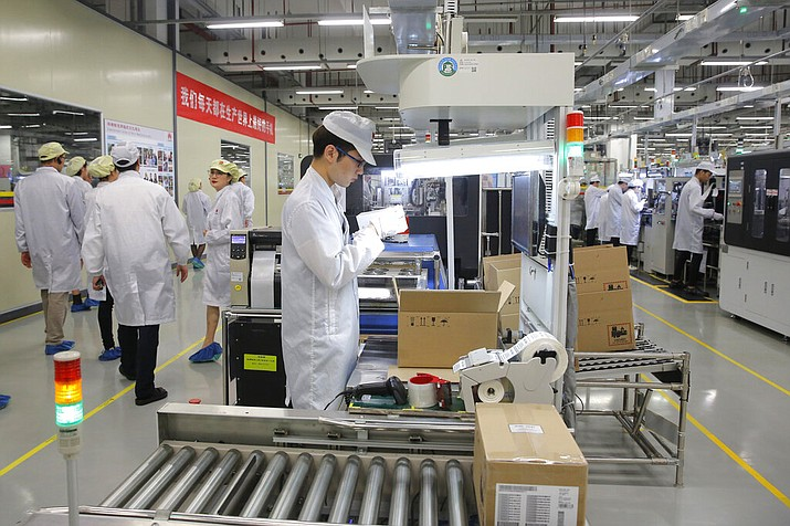 In this March 6, 2019, file photo a staff member works on a mobile phone production line during a media tour in Huawei factory in Dongguan, China's Guangdong province. Huawei Technologies Co. is one of the world's biggest supplier of telecommunications equipment. The United States is delaying tariffs on Chinese-made cellphones, laptop computers and other items and removing other Chinese imports from its target list altogether in a move that triggered a rally on Wall Street. (AP Photo/Kin Cheung, File)