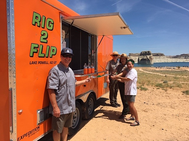 Rig2Flip co-owner Brad Owens and Glen Canyon's Chief of Commercial Services Eric Nikkel along with Glen Canyon Deputy Superintendent Michelle Kerns and Rig2Flip co-owner Kate Sease celebrate the the food truck opening at Lone Rock Beach Aug. 5. (Photo/NPS)