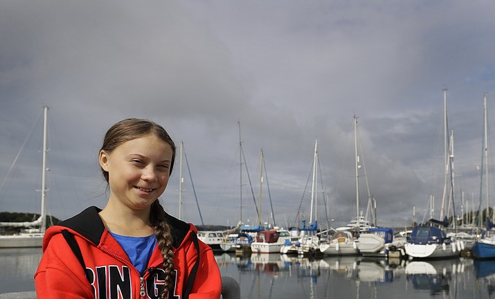 Greta Thunberg poses for a picture in the Marina where the boat Malizia is moored in Plymouth, England Tuesday, Aug. 13, 2019. Greta Thunberg, the 16-year-old climate change activist who has inspired student protests around the world, is heading to the United States this week - in a sailboat. (AP Photo/Kirsty Wigglesworth)