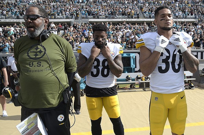 Pittsburgh Steelers wide receivers coach Darryl Drake, left, and running backs Jaylen Samuels (38) and James Conner (30) stand for the singing of the national anthem before an NFL football game against the Jacksonville Jaguars Sunday, Nov. 18, 2018, in Jacksonville, Fla. (Phelan M. Ebenhack/AP, File)