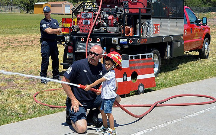 Firefighter Kevin Short of the Pinetop Fire Department helps Andrew Brooks handle a fire hose during the fifth annual White Mountains community Firewise Block Party on July 20, 2019. (Kirk Webb courtesy photo)