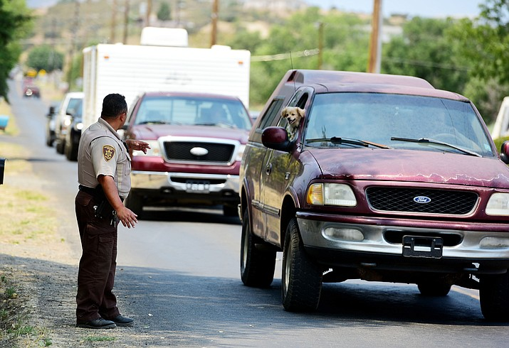 A YCSO Sheriff's deputy directs traffic leaving the Blue Hills area of Dewey-Humboldt after a mandatory evacuation notice was given for the area Wednesday, June 28. (Les Stukenberg/Courier)