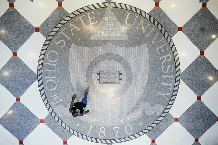 "In this May 18, 2019 file photo, pedestrians pass through Ohio State University's student union in Columbus, Ohio. Ohio State University wants to trademark the word ""The"" when used as part of the school's name on university merchandise. The school submitted a trademark application this month to the U.S. Patent and Trademark Office. The application requests a standard character trademark for the title ""The Ohio State University"" that would cover various items including T-shirts, baseball caps and hats. (AP Photo/John Minchillo)"