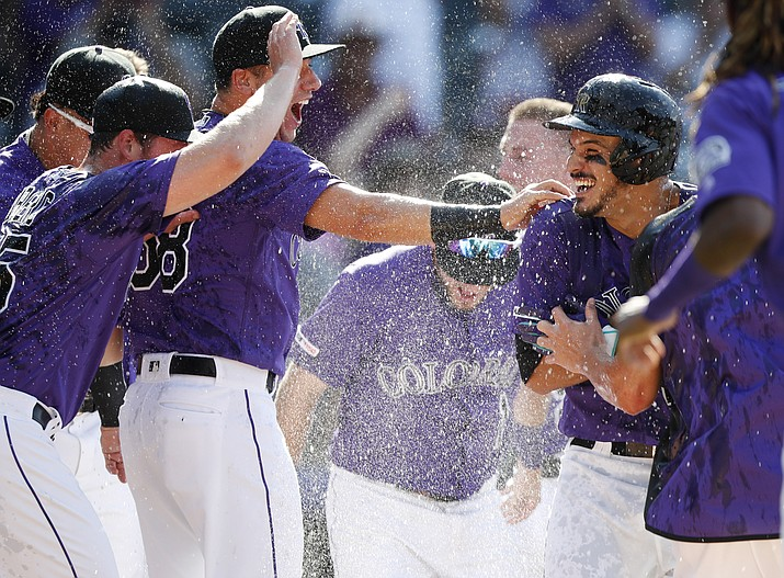 Colorado Rockies' Nolan Arenado, right, is congratulated by teammates after his walk-off two-run home run off Arizona D-backs relief pitcher Archie Bradley during a game Wednesday, Aug. 14, 2019, in Denver. (David Zalubowski/AP)