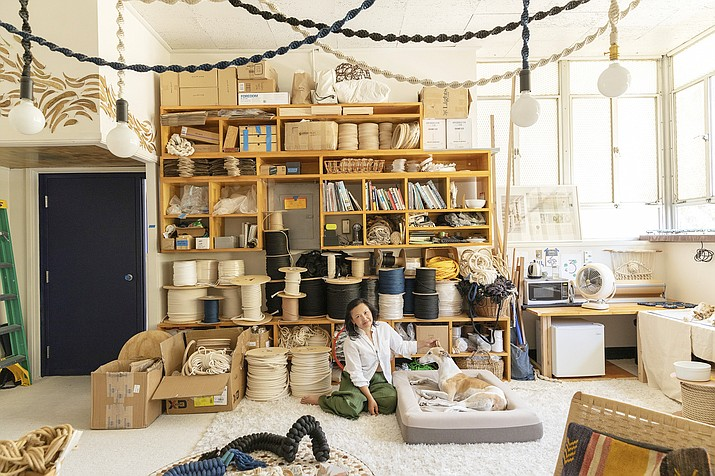 """This undated image shows a photo from the book """"Creative Spaces"""" by Ted Vadakan and Angie Myung, featuring the creative space of Windy Chien, pictured, in San Francisco. (Ye Rin Mok/Chronicle Books via AP)"""