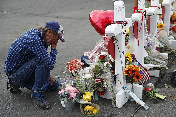 In this Aug. 6, 2019 file photo, Antonio Basco cries beside a cross at a makeshift memorial near the scene of a mass shooting at a shopping complex, in El Paso, Texas. Basco, whose 63-year-old wife was among the Texas mass shooting victims says he has no other family and welcomes anyone wanting to attend her services in El Paso. Margie Reckard was among 22 people fatally shot on Aug. 3 at a the Walmart. Reckard and Basco were married 22 years. (AP Photo/John Locher, File)