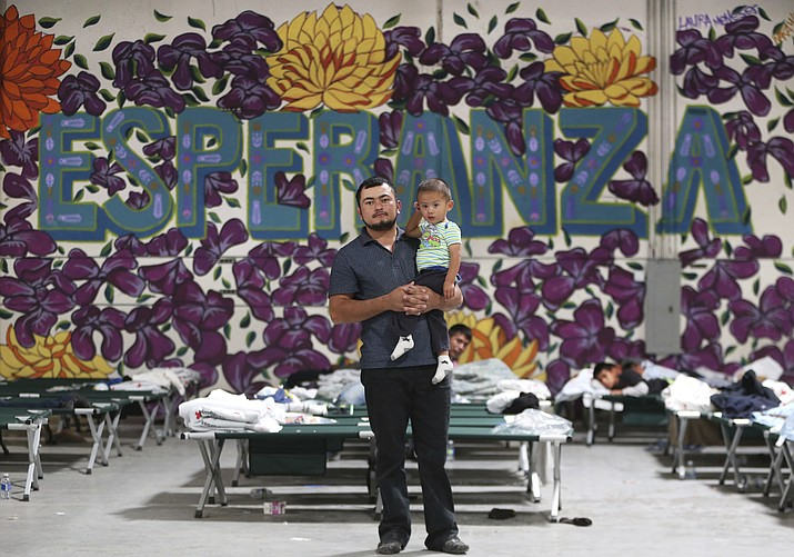 In this Wednesday, April 24, 2019 file photo, a Guatemalan man poses for a photo with his young son at the new Casa del Refugiado in east El Paso, Texas. Behind him is a full-wall mural which reads Esperanza, or hope. A federal appeals court ruling will allow the Trump administration to begin rejecting asylum at some parts of the U.S.- Mexico border for migrants who arrived after transiting through a third country. (Mark Lambie/The El Paso Times via AP, File)