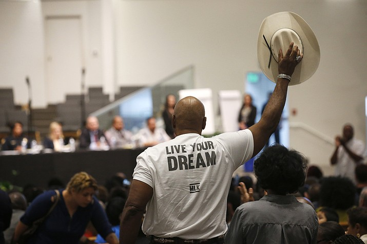 In this June 18, 2019 file photo a Phoenix resident stands up to wave his cowboy hat in support of a speaker at a community meeting in Phoenix. Still stinging from national outrage sparked this summer by a videotaped encounter of officers pointing guns and cursing at a black family, community members are holding low-key meetings aimed at helping Phoenix officials figure out how citizens could help oversee the city's officers. (Ross D. Franklin/AP, File)