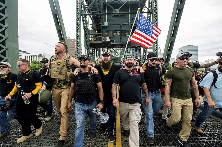 "Members of the Proud Boys and other right-wing demonstrators march across the Hawthorne Bridge during an ""End Domestic Terrorism"" rally in Portland, Ore., on Saturday, Aug. 17, 2019. The group includes organizer Joe Biggs, in green hat, and Proud Boys Chairman Enrique Tarrio, holding megaphone. (Noah Berger/AP)"