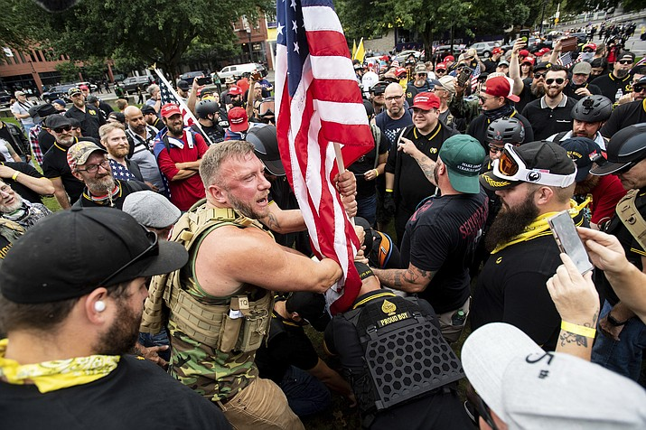 "Joseph Oakman and fellow Proud Boys plant a flag in Tom McCall Waterfront Park during an ""End Domestic Terrorism"" rally in Portland, Ore., on Saturday, Aug. 17, 2019. Portland Mayor Ted Wheeler said the situation was ""potentially dangerous and volatile"" but as of early afternoon most of the right-wing groups had left the area via a downtown bridge and police used officers on bikes and in riot gear to keep black clad, helmet and mask-wearing anti-fascist protesters — known as antifa — from following them. (AP Photo/Noah Berger)"