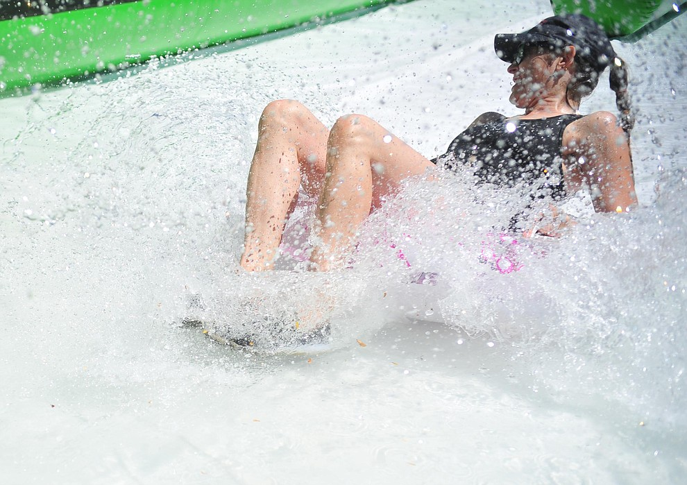 Lori Reynolds on the slide at the annual Monsoon Festival with the water slide that stetches most of the length of Union Street Saturday, August 17, 2019, in downtown Prescott.  (Les Stukenberg/Courier)