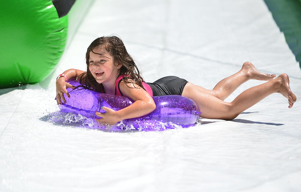 Genesis Scheffer from Prescott Valley is all smiles at the annual Monsoon Festival with the water slide that stetches most of the length of Union Street Saturday, August 17, 2019, in downtown Prescott.  (Les Stukenberg/Courier)