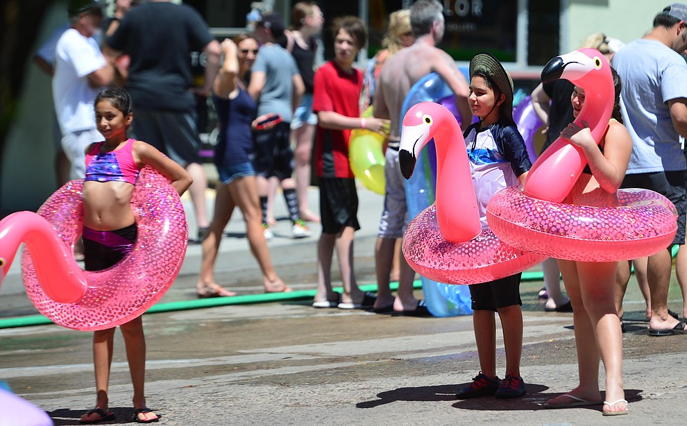 Jenizey Vargas with Sol and Dante Flores brought their own flamongos to the annual Monsoon Festival with the water slide that stetches most of the length of Union Street Saturday, August 17, 2019, in downtown Prescott.  (Les Stukenberg/Courier)