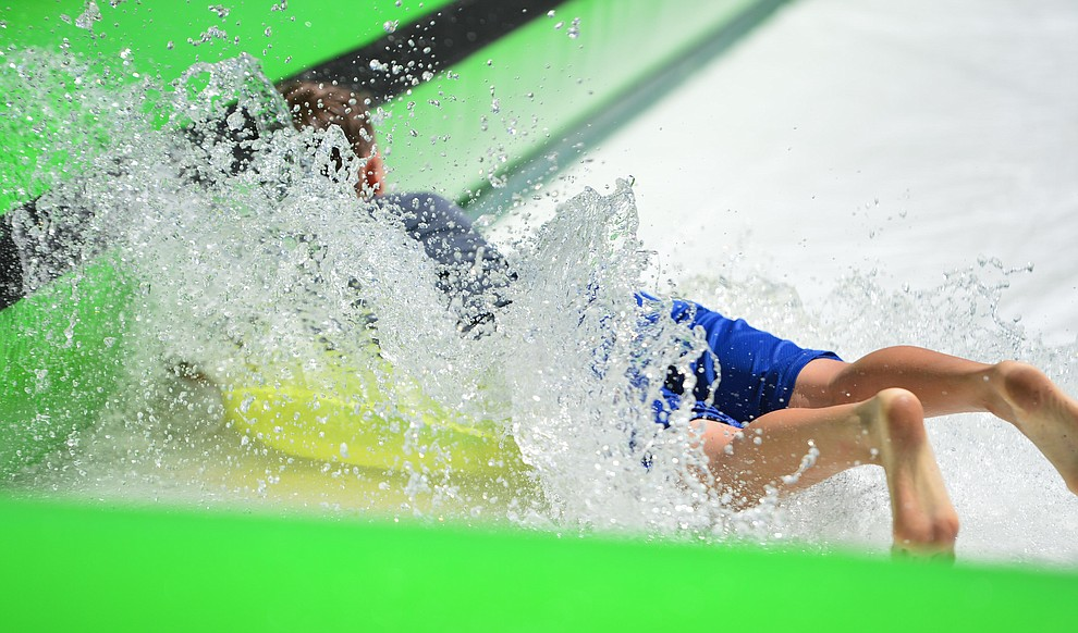 Nate Vandervort hits the bottom of the slide at the annual Monsoon Festival with the water slide that stetches most of the length of Union Street Saturday, August 17, 2019, in downtown Prescott.  (Les Stukenberg/Courier)