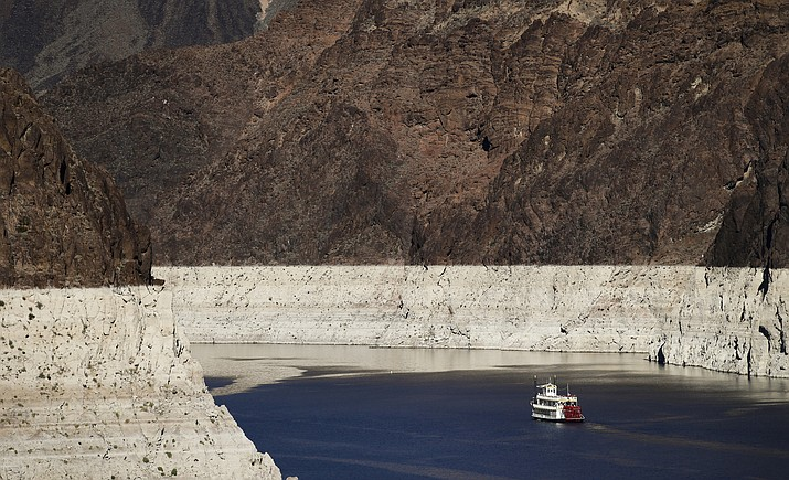 In this Oct. 14, 2015, file photo, a riverboat glides through Lake Mead on the Colorado River at Hoover Dam near Boulder City, Nev. For the seven states that rely on the Colorado River that carries snowmelt from the Rocky Mountains to the Gulf of California, that means a future with increasingly less water for farms and cities although climate scientists say it's hard to predict how much less. The U.S. Bureau of Reclamation released its projections for next year's supply from Lake Mead, which feeds Nevada, Arizona and California. (AP Photo/Jae C. Hong, File)